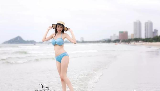 身穿比基尼的泰妹,走在阳光下的沙滩上